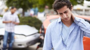Teenage Driver Suffering Whiplash Injury Traffic Accident Rubbing Neck With Hand.