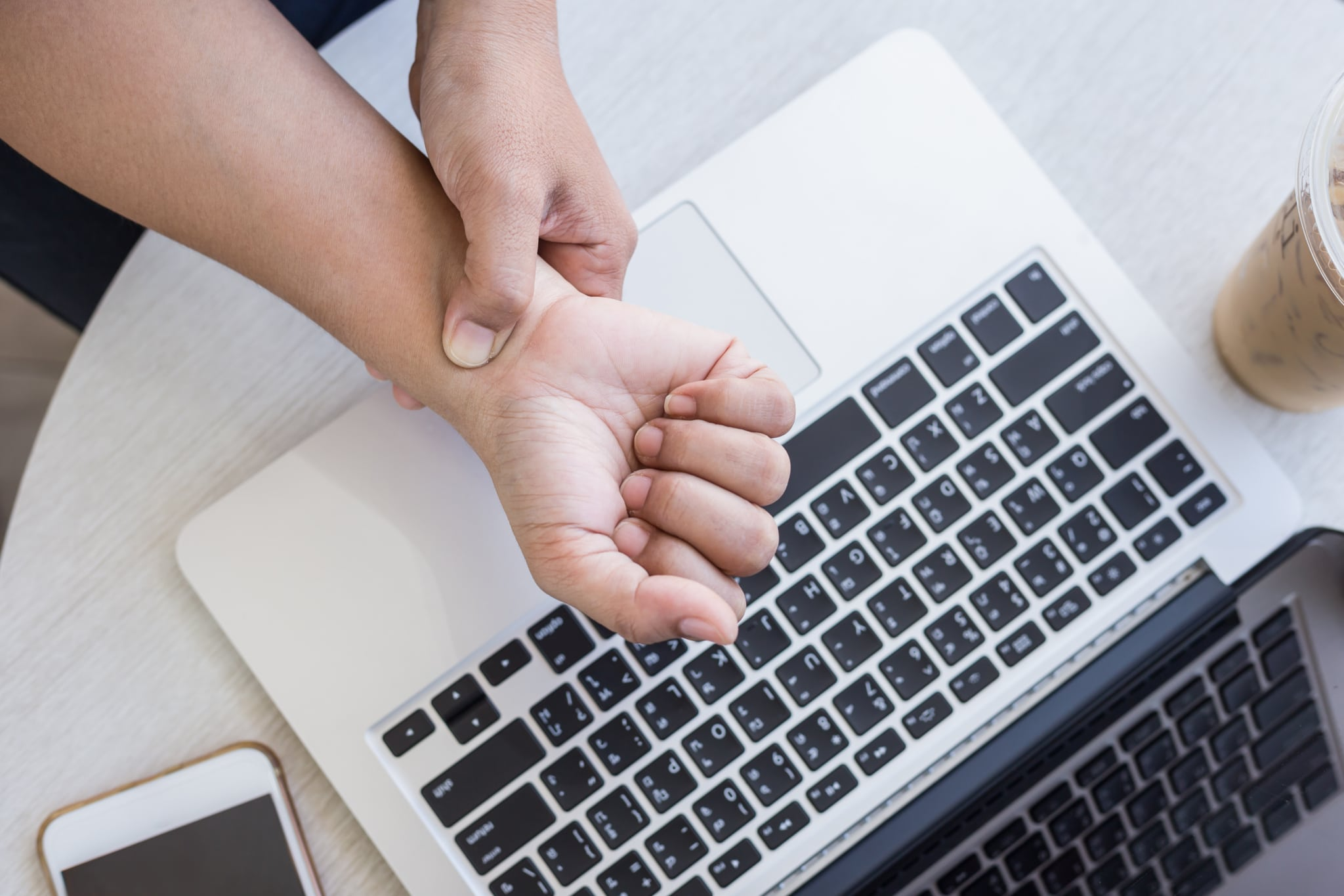 Person rubbing wrist in pain while working on computer