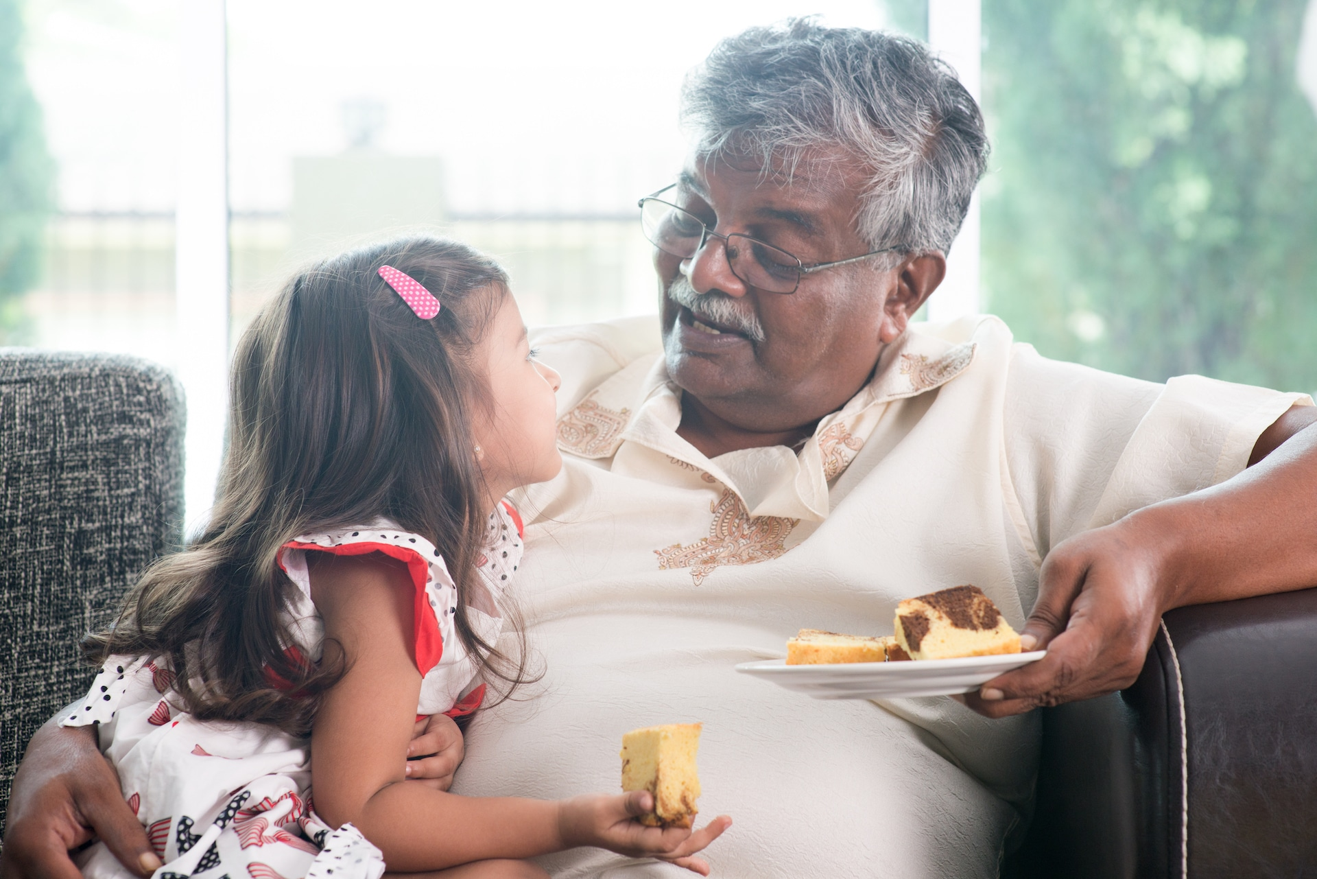 Grandfather and granddaughter eat cake