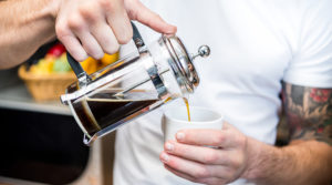 a man pours coffee for himself from a french press