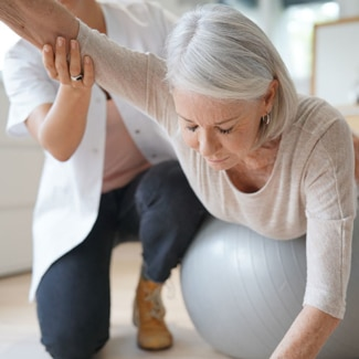 Older woman stretching arm out on a medicine ball with the help of a female physical therapist
